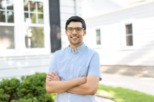 man smiling in front of house