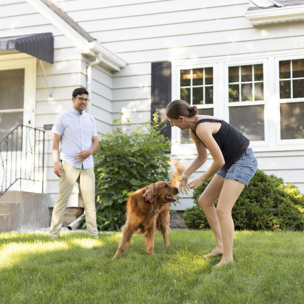 couple smiling on the lawn with dog