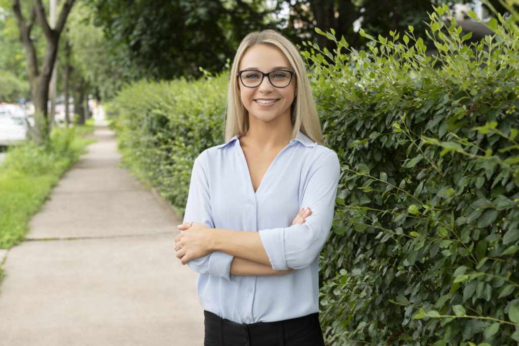 woman smiling near bushes